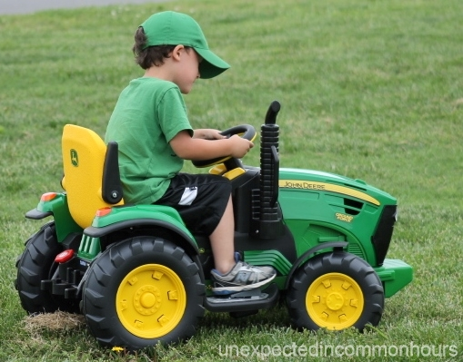 B. driving his John Deere